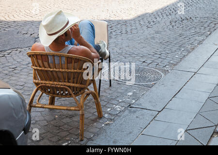 Naples, Italy - August 9, 2015: Illegal parking valet, strong man sitting on the roadside for car place reservation - Stock Photo