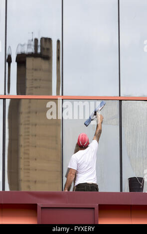 Sanitation worker cleaning glass facade - Stock Photo
