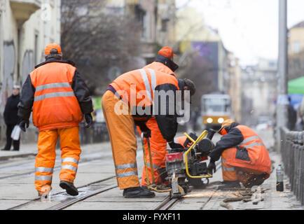 Tram road workers repair repairing - Stock Photo
