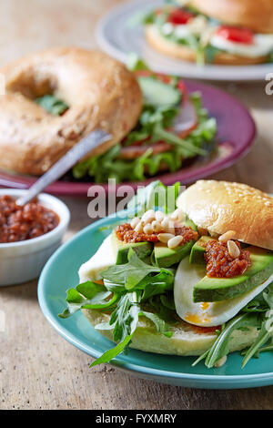 Fresh bagel sandwiches on wooden table - Stock Photo