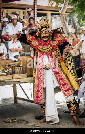 Balinese man in mask performing at Kuningan Ceremony during the Galungan Religious ceremony in Bali - Stock Photo