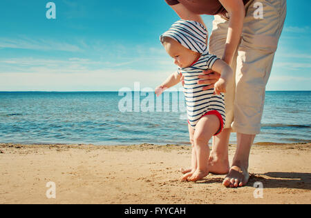 Little baby boy walking on the beach in summer day Stock Photo