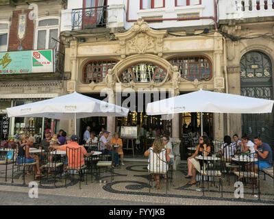People enjoying and having drinks on outdoor terrace of famous Cafe Majestic on Rua Santa Catarina in Porto, Portugal - Stock Photo