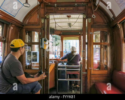 Driver and tourist inside vintage tramcar of heritage tram line in Porto city, Portugal - Stock Photo