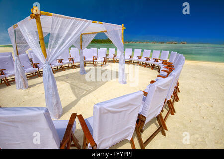 Decorated chairs and arch for wedding ceremony on tropical island with sandy beach and tourquise clear water - Stock Photo