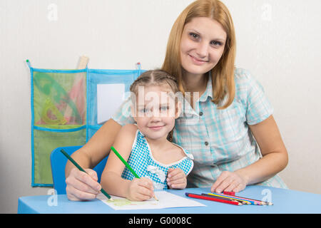 Five-year girl and young mother together paint a picture on a sheet of paper - Stock Photo