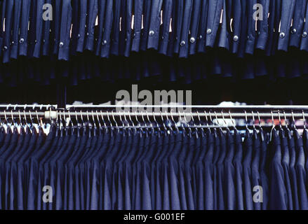 Rows of new tuxedos on a rack in a garment manufacturing facility - Stock Photo