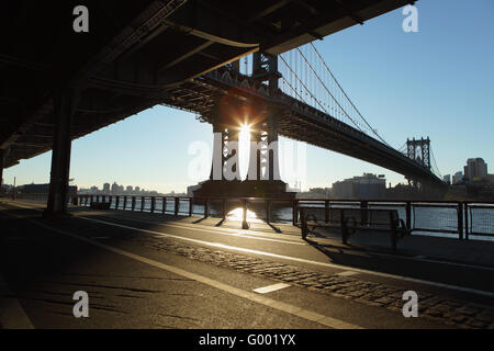The sun rises over Brooklyn and casts deep shadows on the East River Esplanade, New York - Stock Photo