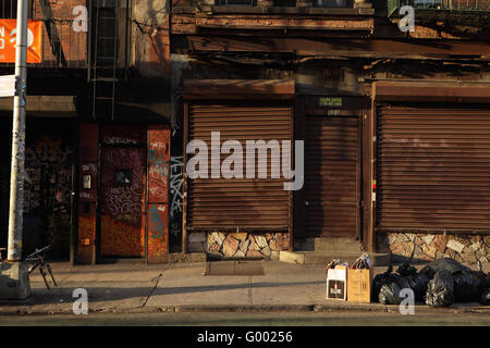 Old brick tenement building on Rivington Street, Lower East Side, New York City. Shop has security shutters down - Stock Photo