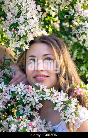 Pretty woman among a spring blossom - Stock Photo