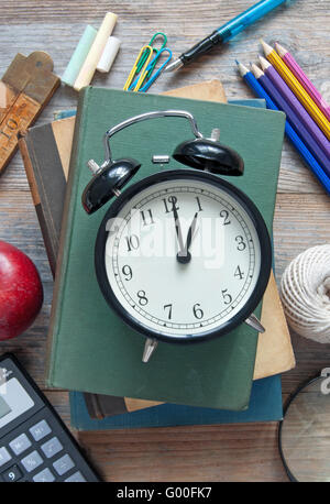 Clock on top of a book and various school and stationery accessories - Stock Photo