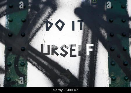 LONDON, UK - JANUARY 13TH 2016: The words 'Do it uself' sprayed onto a brick wall in London, on 13th January 2016. - Stock Photo