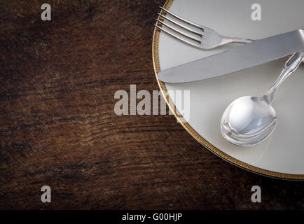 Close up Silver Spoon, Fork and Knife Tied on White Dish, on wooden talbe - Stock Photo