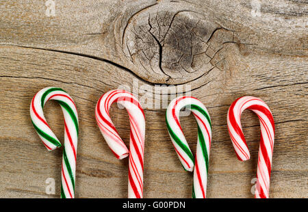 Candy canes on rustic wooden board - Stock Photo