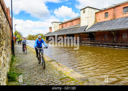 Cyclists on towpath of Leeds and Liverpool Canal opposite Wigan Pier in Wigan Greater Manchester UK - Stock Photo