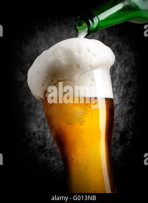 Beer pouring into glass on black background - Stock Photo
