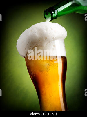 Beer pouring into glass on green background - Stock Photo