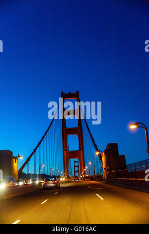Crossing the Golden Gate Bridge at night just after sunset - Stock Photo