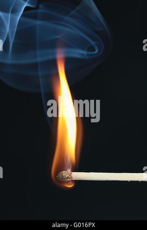 ignited match with blue smoke on black background - Stock Photo