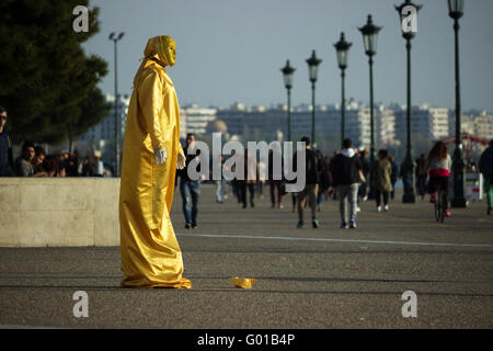 A street busker mime artist wearing a gold reflective sequin dress working for gratuities on Salonika's New waterfront - Stock Photo