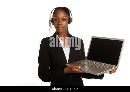 young female customer service representative with her headset on ready to work at her laptop - Stock Photo