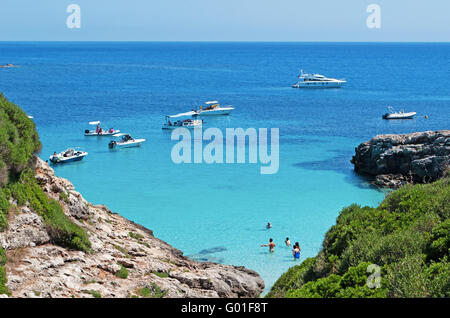 Menorca, Balearic Islands: boats and tourists on a menorcan beach. The island has a variety of beaches, crowded - Stock Photo