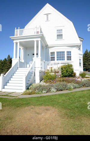 exterior of an old white house on the Maine coast.  The house is white, with steps leading to the front door.  There - Stock Photo