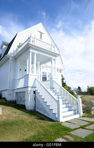 exterior of an old white house on the Maine coast.  The house is white, with steps leading to the front door and - Stock Photo