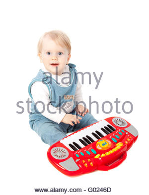 pretty little baby girl pianist plays on a toy piano synthesizer isolated on white - Stock Photo