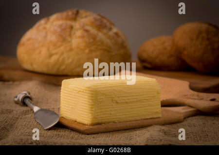 Hand churned homemade butter on wooden paddles with butter knife and loaf of bread. - Stock Photo