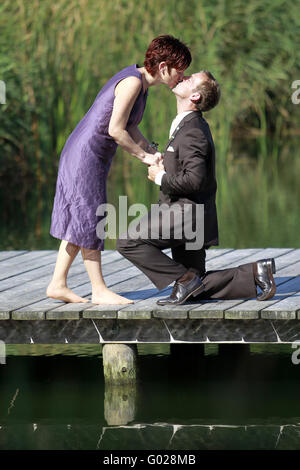 a couple in love on the pier at the lake - Stock Photo