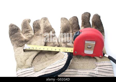 Retractable steel tape and leather work gloves on  white background. - Stock Photo