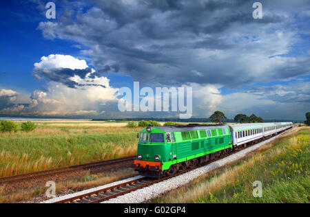 Intercity train passing through countryside with colorful sky over - Stock Photo