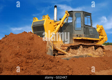 Close view of heavy bulldozer moving sand in sandpit - Stock Photo