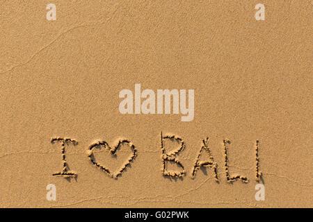 I love Bali - the inscription by hand on the beach sand. - Stock Photo