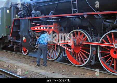 Man doing the repair on the old steam locomotive - Stock Photo