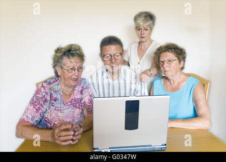 Seniors group with a teacher on the computer - Stock Photo