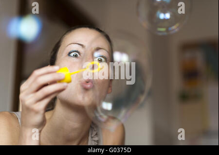 Young woman blowing soap bubbles into the air - Stock Photo