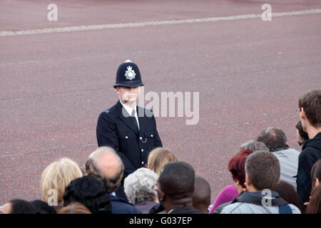 British policeman observes crowd - Stock Photo