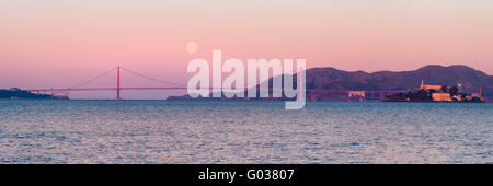 Panoramic of Full Moon Setting Behind the Golden Gate Bridge with Alcatraz - Stock Photo