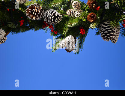 Festive christmas decoration with pine cones on blue sky with copy space - Stock Photo