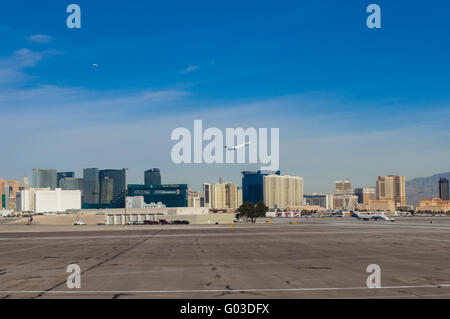 Jet aircraft taking off from McCarran International Airport with Las Vegas casinos in the background.  Las Vegas, - Stock Photo