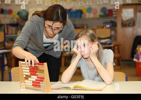 a teacher and pupil count together in school - Stock Photo