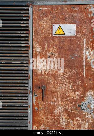 danger high voltage sign on a rusty metal door - Stock Photo
