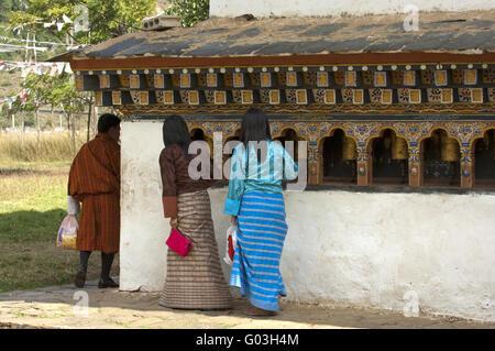 Young Bhutanese turning the prayer mills, Bhutan - Stock Photo