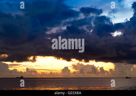 Sunset at South China Sea with threatening sky and - Stock Photo