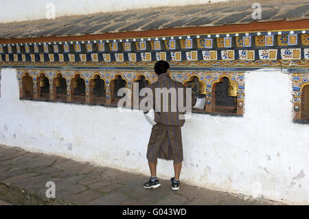 Bhutanese man at a prayer mill in the Temple - Stock Photo