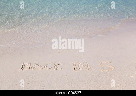 Back in 5 written out in wet sand, Thailand - Stock Photo