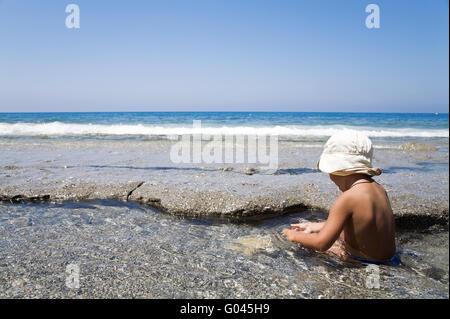 little boy plays on an ocean coast in summer day - Stock Photo