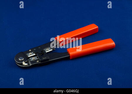Rj11 connectors and telephone cable crimper isolated on a blue background - Stock Photo